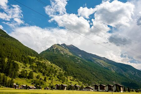 Amazing view of the typical chalets and green slopes of the Swiss Alps. Colorful summer view of village. Idyllic outdoor scene in Switzerland, Europe