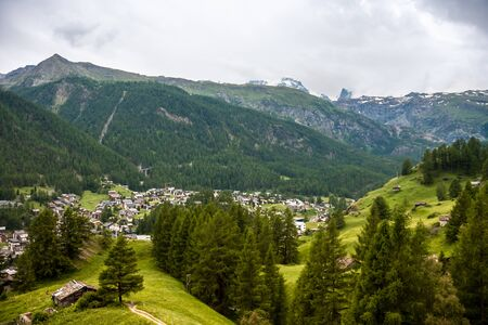 View of resort Zermatt on Alpine valley landscape, mountain, green meadow, coniferous forest.