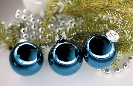 Christmas balls blue on green spruce branch.