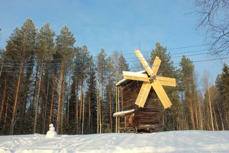 Beautiful winter landscape. Old wooden windmill in village