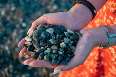 Handful of green pebbles in hands. Perfect clean pebble beaches on the coast of Liguria Stock fotó