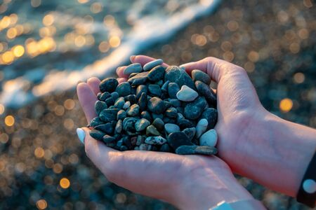 Girl holds a handful of green pebbles. Against the background of the sea.