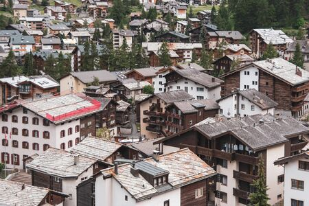 View of the roofs of chalets in a Swiss resort. A place preserving authentic architecture. Natural stone roofs, wooden facades