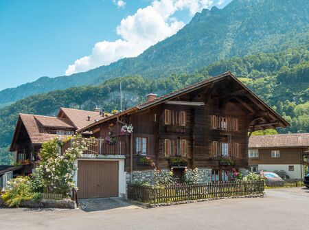 Beautiful traditional wooden house in the alpine village, Switzerland. House decorated with flowers, near flowerbed Imagens
