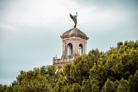 The statue on the roof of the old church can be seen from the tops of the trees.