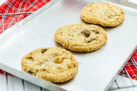Fresh baked chocolate almond cookies on silver tray that lie on red tartan dishtowel photo