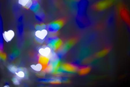 Blurred white heart shape bokeh on rainbow light background