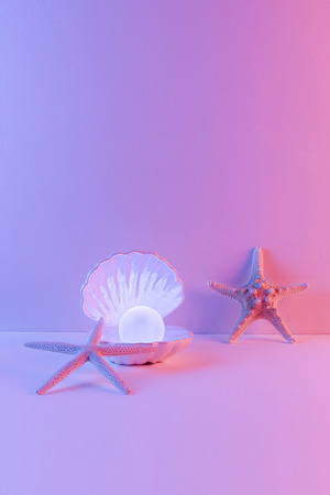 Pastel neon blue and pink light paint on seashell and pearl decorate with star fish