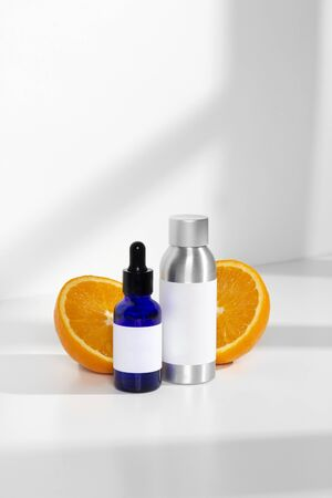 Blue glass and silver metal skin care bottle decorate with fresh half oranges on window light white background photography
