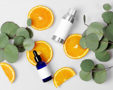 Blue glass and silver metal skin care bottle decorate with fresh half oranges and leaves on white background photo