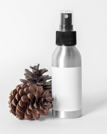 Silver spray skin care bottle decorate with pine cones on white background photo