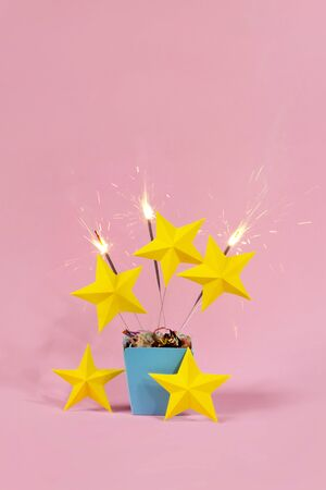 Five stars review with yellow star shape and sparklers exploding from blue gift box on pastel pink background photo