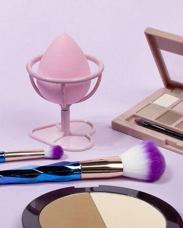 Pastel make-up tool included blender sponge brush powder brush on on purple background