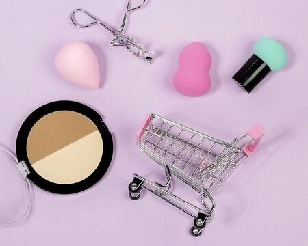 Pastel make-up tool included blender sponge brush powder eyelash curler on purple background