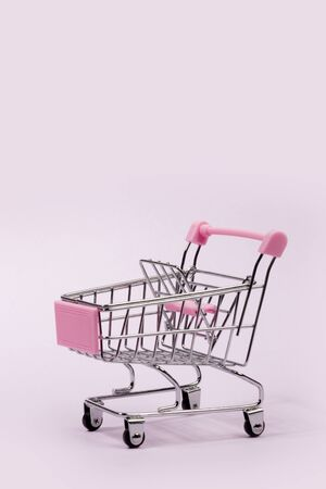Pastel pink miniature shopping cart on pink background Фото со стока