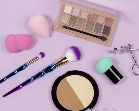 Pastel make-up tool included blender sponge brush powder brush on on purple background
