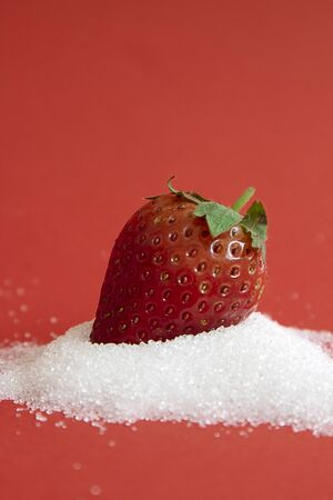 Red Strawberry drops on white sugar on red background photography