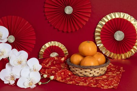 Lucky Chinese new year celebration with orange red Ang Pao money Cheongsam and oriental orchid flower on red background photography Фото со стока