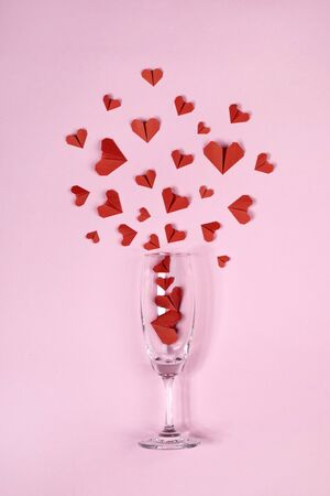 Red heart shaped paper origami explode from champagne glass on pink background for Valentine's day poster photography