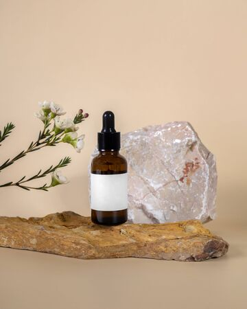 Facial oil in brown glass bottle display on beige stone decorate with flower on beige background photography
