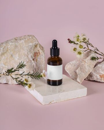 Facial oil in brown glass bottle display on pastel pink stone decorate with flower on pink background photography