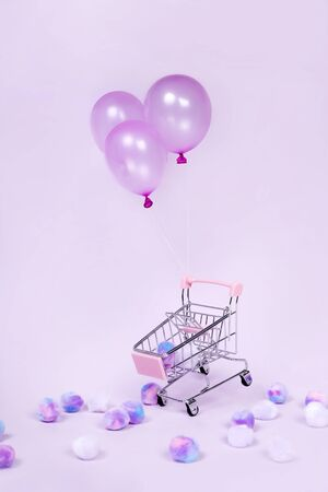 Pastel pink shopping cart floating with balloon on pink background photography
