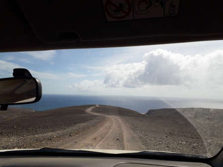 path leading to the ocean through car window. to the uncertain future, ready for adventure and new challenges. unbeaten path