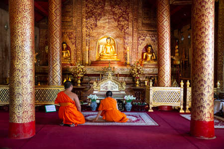 two monks praying in the interior of a buddhist temple in Chang Mai, Thailand