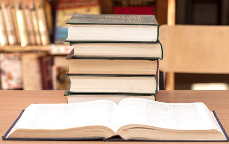 scientific literature: The open book and pile of books in library