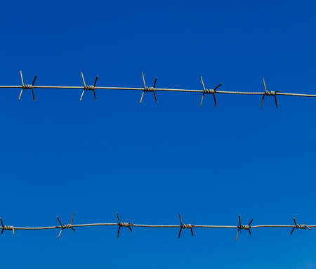 part prison: barbed wire against the blue sky