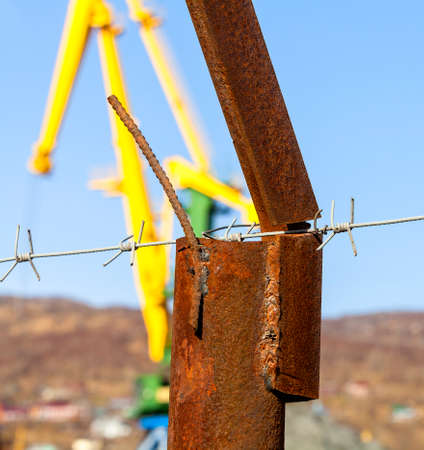 part prison: barbed wire on the rusty post against the blue sky and cranes Stock Photo