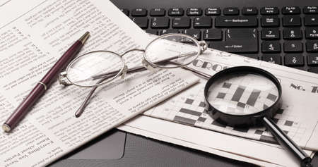 old newspaper: glasses and old newspaper lying on the black open laptop Stock Photo