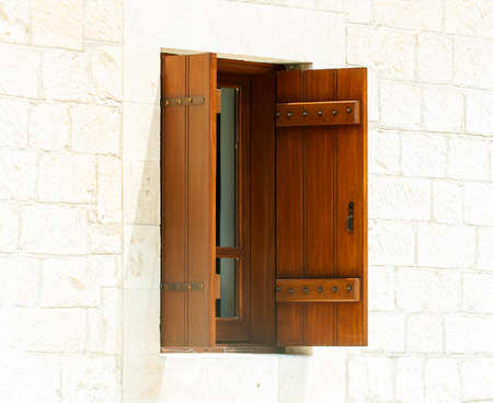 wooden window: open wooden window against a white stone wall