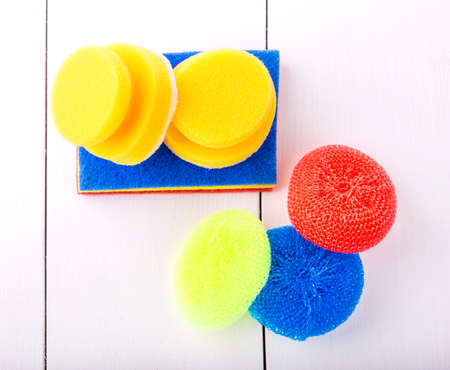 scour: New yellow, red and blur sponge for washing dishes on a white background shot from above