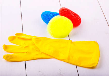 yellow rubber gloves and collored sponges  on a white wooden table Stock Photo