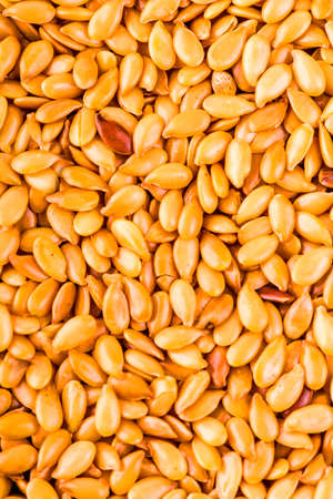 linum: Background texture of roasted golden flax seed or linseed with healthy omega-3 fatty acids, dietary fiber, rich in oils and used to lower cholesterol Stock Photo