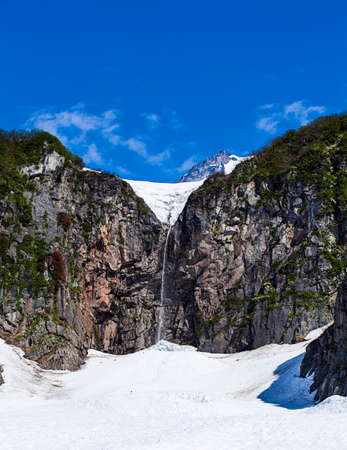 volcano slope: waterfall on the slope of the volcano Viluchinsky from melting snow in the spring in Kamchatka