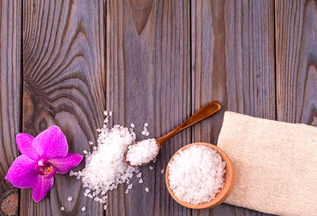 White bath salt in a wooden bowl with a spoon, soap, burlap and orchid on wooden table