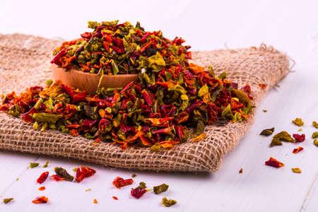 Especias coloreadas con pimienta en una taza y arpillera en una mesa de madera