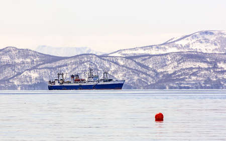 trawler net: large fishing vessel on the background of snow-covered hills and volcanoes in the Avacha Bay in Kamchatka Stock Photo