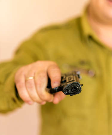 Man pointing gun at the target with one Hand,selective focus on front gun.