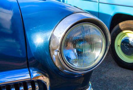 shiny car: Blue vintage car on a festival of old cars. Retro cars headlight close up.