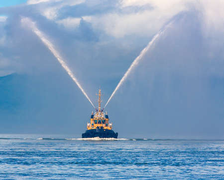 fire hose boat spraying water on Kamchatka on Paciic ocean Stock Photo