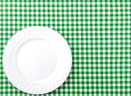 White Plate on Green and White checkered Fabric Tablecloth Background