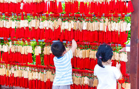 China, Sanya - 15 Nov 2017: Chinese children hang EMA in a Buddhist temple Editorial