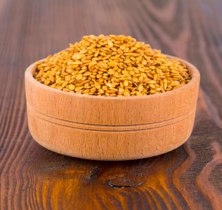 Brown flax seeds in a wooden bowl on wooden sufface