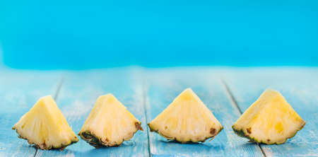 Spring or summer concept : Close up patter of many pieces of yellow pineapple  on blue wooden table background.