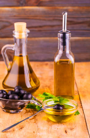 Olive Oil. Bottle of Virgin Olive Oil. Olives and Healthy Olive oil bottles and cup with parsley on old wooden table. Stok Fotoğraf