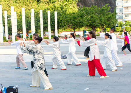 Sanya, China : 11 NOV 2017: Women and men in the street in the Park gymnastics WUSHU.