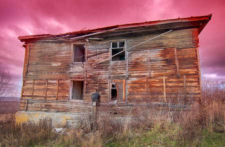 Vieja y fea casa de madera en ruinas sobre un fondo de cielo rojo al atardecer